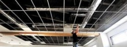 Construction worker installing ceiling at Bozeman High